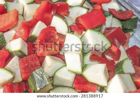 A background of red pepper and green zucchini dices - stock photo