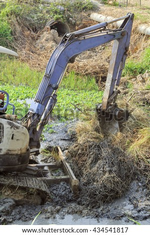 A backhoe loader cleans up mud and weed on a river, Thailand.  - stock photo