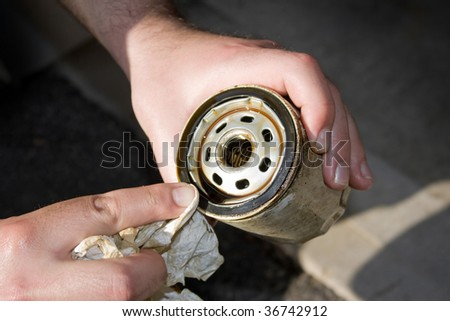 A backyard mechanic wipes the seal of  a slightly used oil filter to reuse it for an additional 3000 miles.  Others prefer to replace them each and every oil change. - stock photo