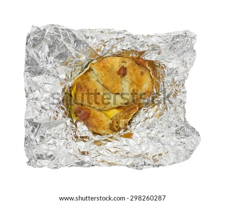 A bacon egg and cheese croissant breakfast sandwich with a bit of bacon on the crust on aluminum foil isolated on a white background. - stock photo