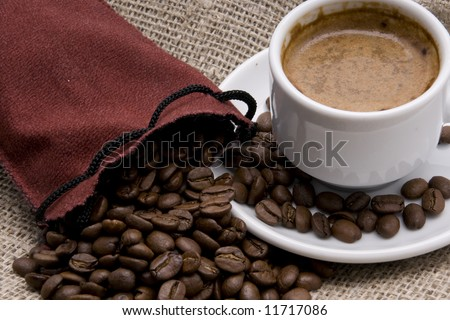 A bag filled with coffee-beans and white cup of coffee - stock photo