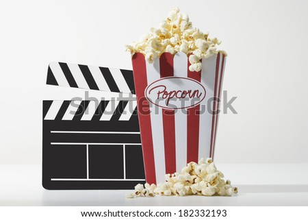 a bag full of popcorn and a black clapper board with white background - stock photo