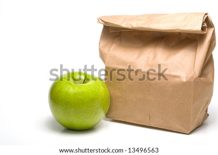 A bag lunch with a Granny Smith apple. - stock photo