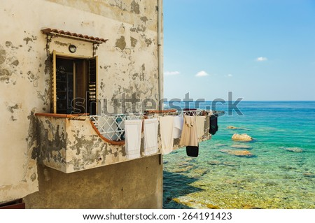A balcony with drying linen overlooking the sea in Scilla, Calabria, Italy. - stock photo