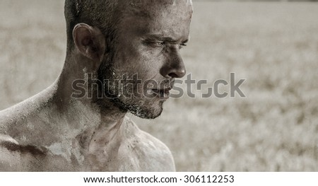 A bald man walking in the field in the mud, sand and clay without clothes. - stock photo