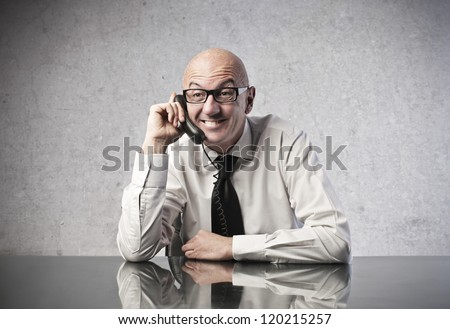 A bald office worker smiles while is calling someone with a mobile phone - stock photo