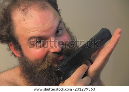 A balding bearded man mugs for the camera while displaying his pistol - stock photo