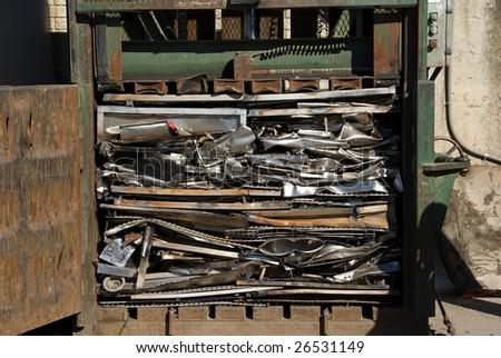 A baler compacting scrap metal - stock photo