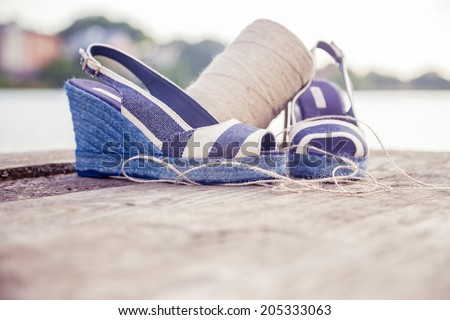 A ball of yarn around women sandals, shoes outdoors - stock photo