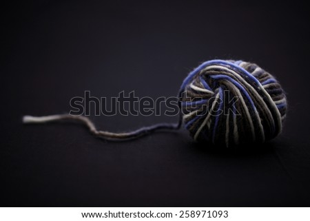 a ball of yarn on dark background - stock photo