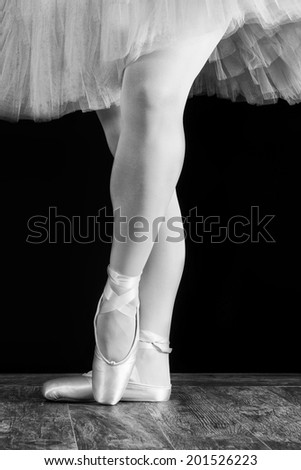 A ballet dancer standing on toes on black background artistic conversion - stock photo