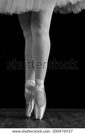 A ballet dancer standing on toes while dancing on black background  - stock photo