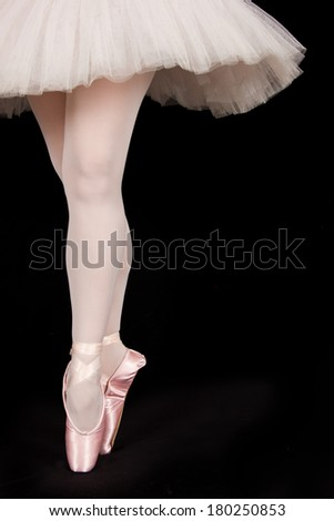 A ballet dancer standing on toes while dancing on black background artistic conversion - stock photo
