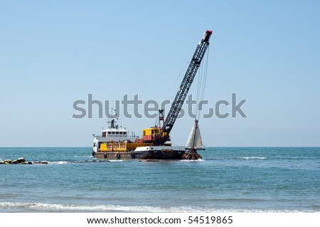 A barge is dredging a harbor removing stones and sand - stock photo