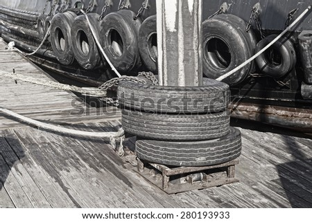 A barge with a series of tires along its hull for use as bumpers when interacting with other vessels.  - stock photo