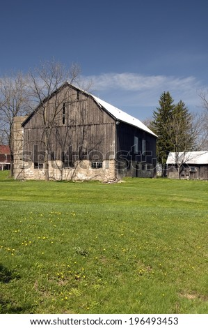 A barn adjacent to smaller buildings, surrounded by trees, on a sunny day. - stock photo
