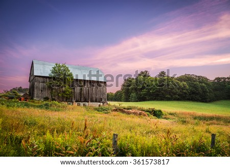 A barn in the countryside with tall grass and trees at sunset. - stock photo