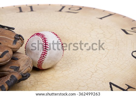 A baseball and mitt on an old vintage clock on an isolated white background - stock photo