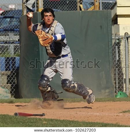 A baseball catcher throws to first base to check the runner. - stock photo