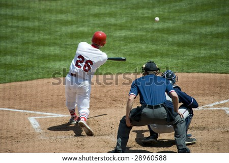 A baseball game with a batter, catcher and umpire on a beautiful sunny day - stock photo