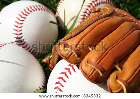 A baseball glove surrounded by balls on a field - stock photo