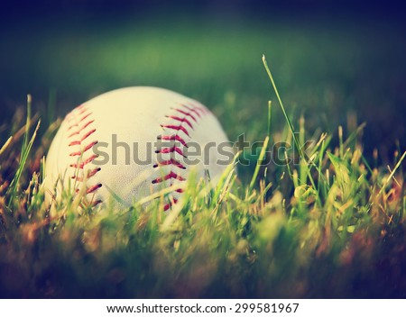 a baseball in a grass background toned with a vintage retro instagram filter effect app or action  - stock photo