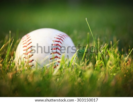 a baseball in a grass during sunset  - stock photo
