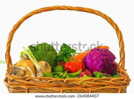 A basket filled with freshly picked vegetables on White background - stock photo