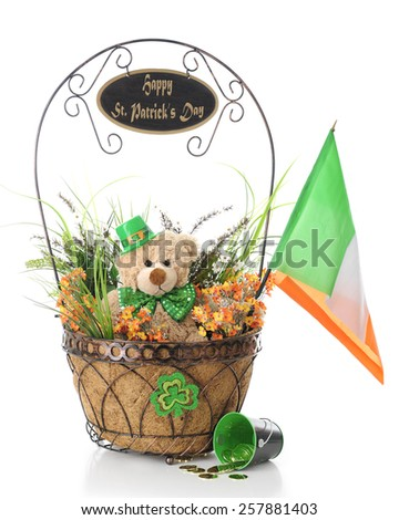 """A basket filled with orange and green foliage, toy bear with green tie and hat, and an Irish flag.  The basket's  handle is adorned with a """"Happy St. Patrick's Day"""" sign.  On a white background. - stock photo"""