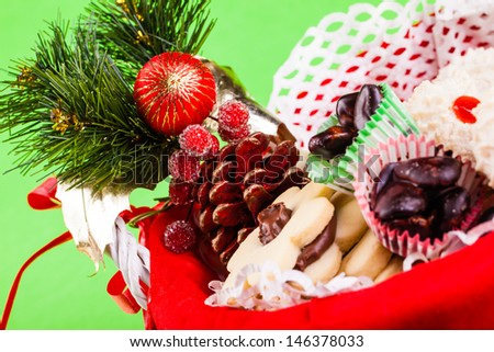 a basket full of delicious christmas pastry on a green background - stock photo