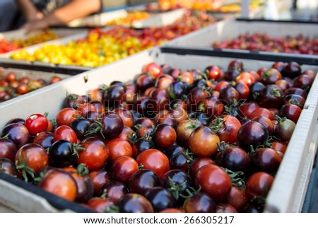 A basket full of purple cherry bombs for sale in a street market - stock photo