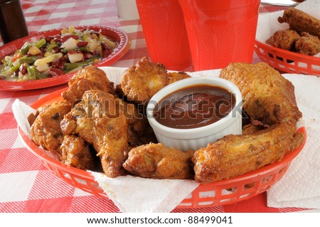 A basket of chicken wings on a plastic picnic tablecloth - stock photo