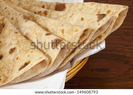 A basket of homemade chapatis, popular Indian bread for eating with curry. - stock photo