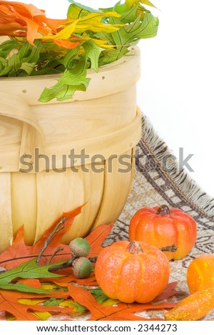 A basket of multi-colored leaves, some acorns and pumpkins complete this seasonal autumn scene. - stock photo