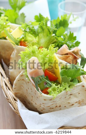 A basket of pita bread pockets filled with ham and salad.  Healthy eating. - stock photo