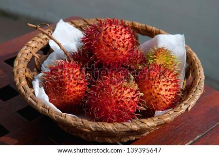 a basket of tropical rambutan fruit - stock photo