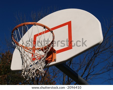 A basketball hoop extending out into a bright blue sky - stock photo