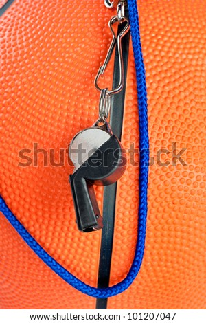 A basketball referee's whistle draped over an orange, rubber basketball. Good for sports inferences where rules are important. - stock photo