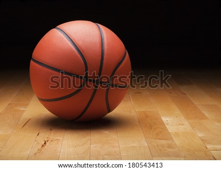 A basketball with a dark background on a hardwood gym floor - stock photo