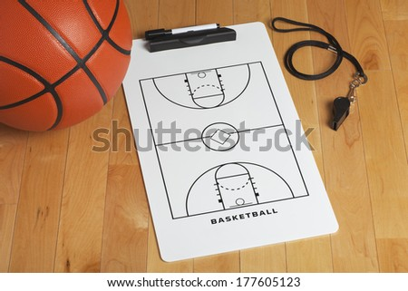 A basketball with coach's clipboard and whistle on a wooden gymnasium floor - stock photo