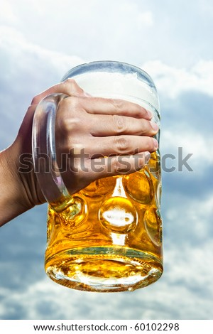 A Bavarian beer held against a dramatic cloudy sky - stock photo