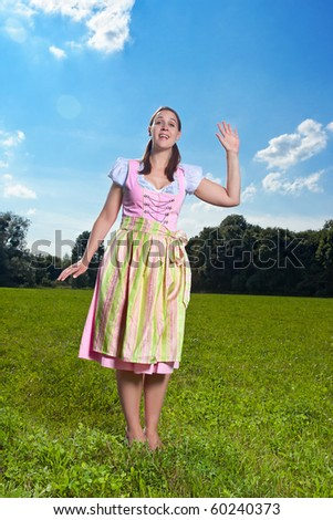 A Bavarian girl in traditional costume in a field waving a greeting - stock photo
