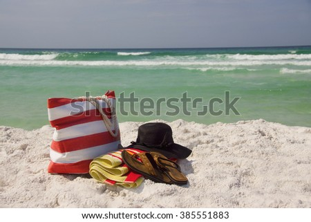 A beach bag, floppy hat, towel and Sandals at the beach. - stock photo