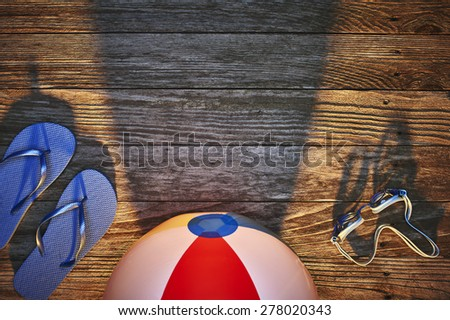 a beach ball, goggles and sandals on a dock at sunset - stock photo