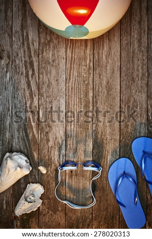a beach ball, sandals, shells and swimming goggles on a dock at sunset - stock photo