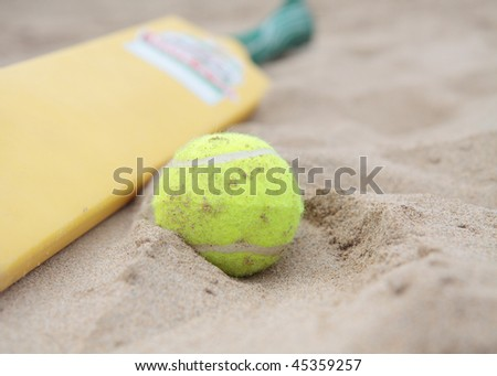 A beach cricket bat with tennis ball on the sand. - stock photo