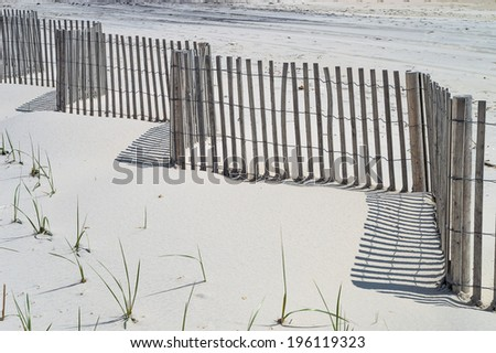 A beach fence casts shadows on the mid-day sun in Surf City along the New Jersey shore. - stock photo
