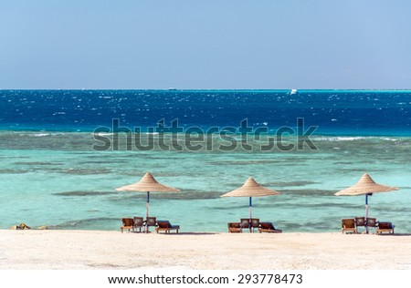 a beach umbrella on the background sand, sea, sky and corals - stock photo