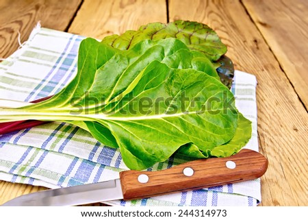 A beam of red and yellow chard, knife, napkin on a wooden boards background - stock photo
