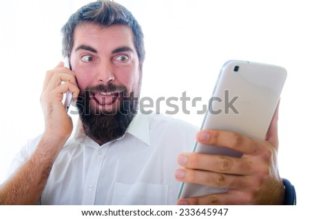 A beard man talking by smartphone while he puts funny faces - stock photo